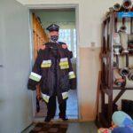 Strażak prezentuje strój bojowy