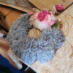 Wianek wykonany z włóczki, wraz z kwiatowymi ozdobami