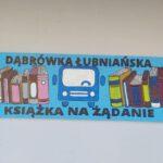 """Kolorowy napis """"Dąbrówka Łubniańska. Książka na żądanie"""" przytwierdzony do ściany przystanku"""