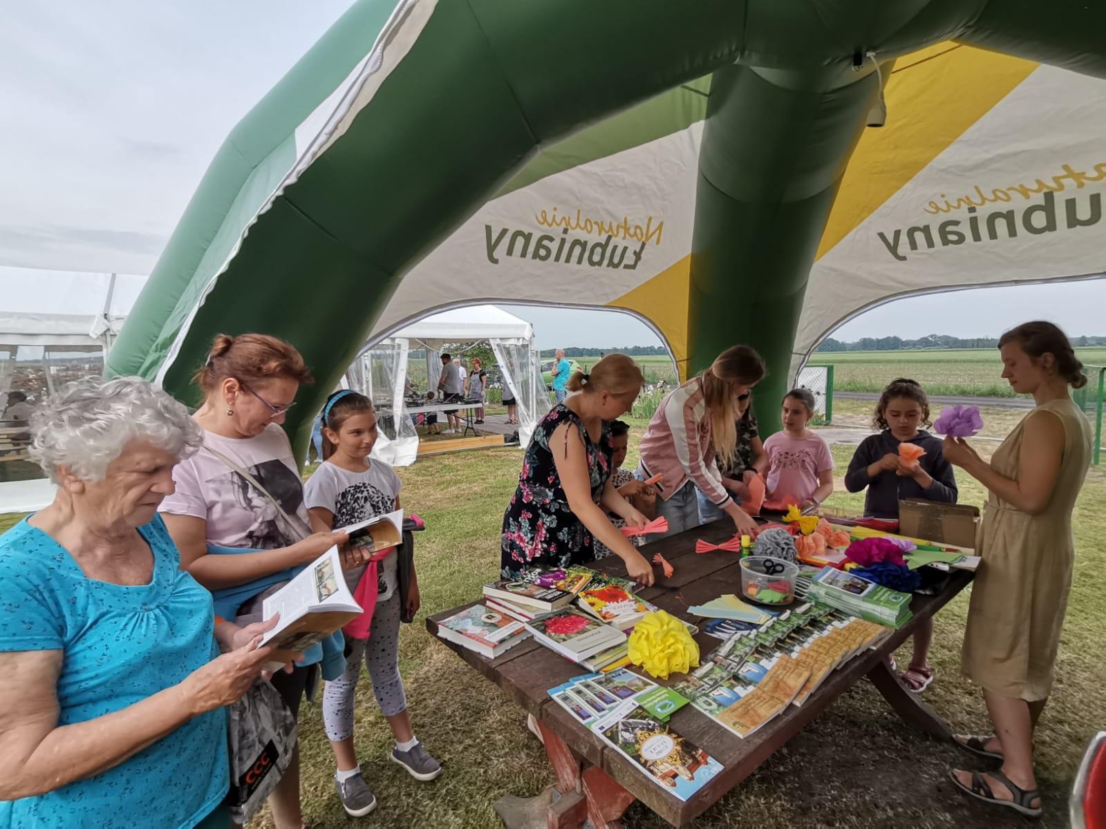 uczestnicy warsztatów (dzieci robiące kwiaty oraz seniorzy czytający ksiażki)